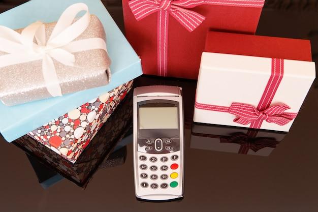 Terminal, pudełka z prezentami na stole z czarnego szkła. koncepcja zakupów na prezenty.