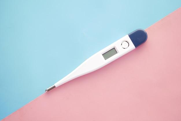 Termometr cyfrowy na różowym tle z miejscem na kopię