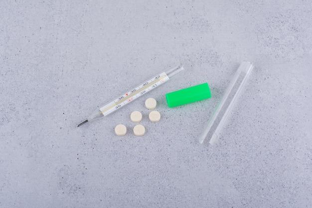 Termometr i medyczne pigułki na marmurowym tle. zdjęcie wysokiej jakości