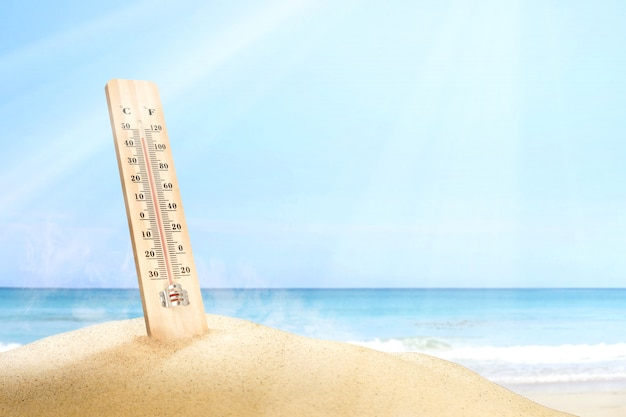 Termometr mierzący temperaturę na plaży z niebieskiego nieba tłem