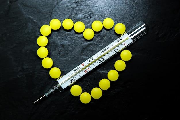 Termometr rtęciowy o temperaturze 36,6. zdrowa osoba. pigułki w formie serca na tle. zdrowy układ krążenia. koncepcja wirusa.