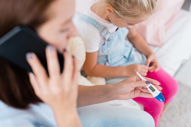 Termometr trzymany przez młodą matkę wzywającą lekarza do domu dla chorej córki, siedząc obok dziecka