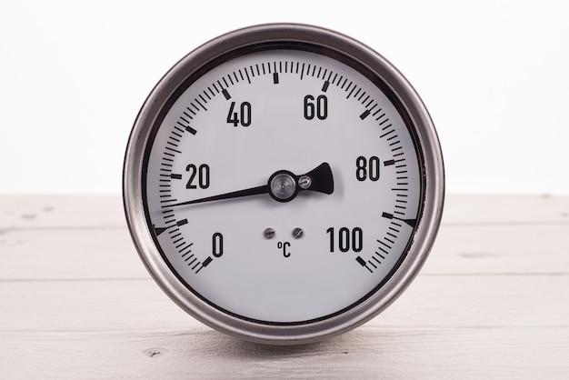 Termometr zegarowy na białym drewnianym