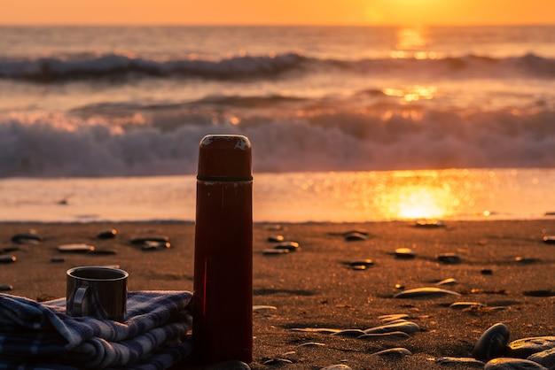 Termos gorącej herbaty i miękki pled na piaszczystej plaży wczesnym rankiem beach