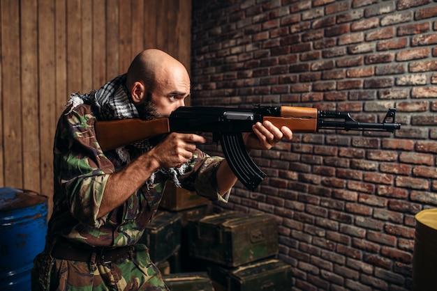 Terrorysta celujący z karabinu kałasznikowa