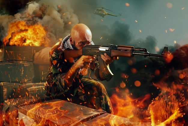 Terrorysta strzela z karabinu, wszystko w ogniu