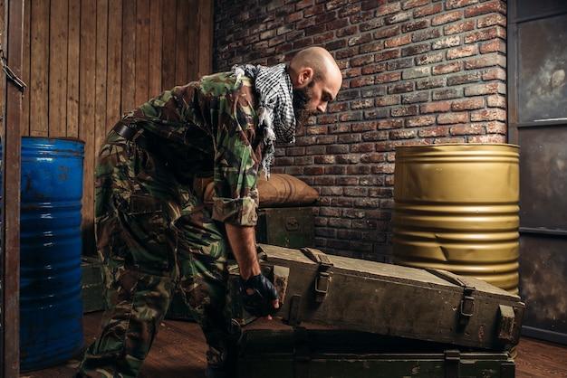Terrorysta w mundurze ładuje skrzynie z amunicją. terroryzm i terror, żołnierz w kamuflażu uzupełnia arsenał