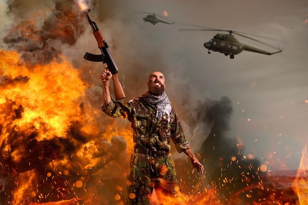 Terrorysta z karabinem stoi w wybuchu i pożarze