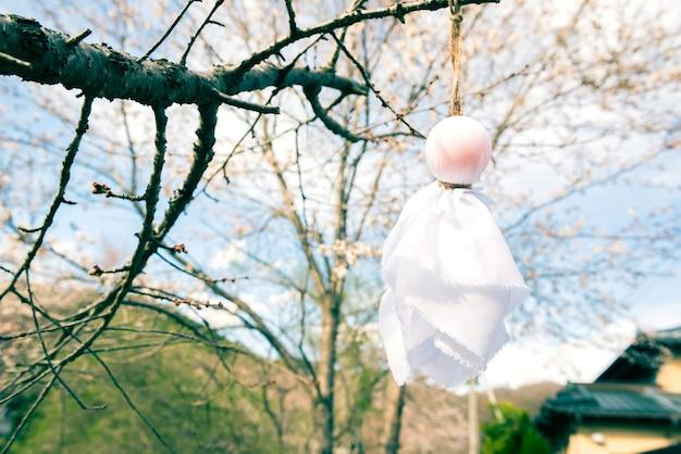Teru teru bozu. japońska lalka rain wisząca na drzewie sakura, aby modlić się o dobrą pogodę