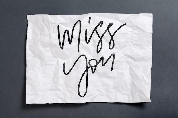 Tęsknię za tobą. odręczny tekst na białym zmiętym papierze.