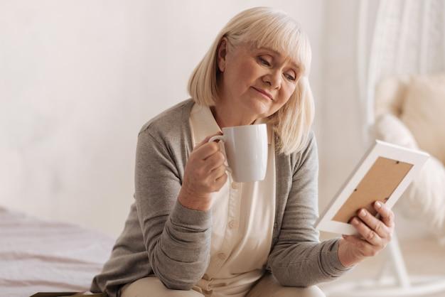 Tęsknię za tobą. smutna, zamyślona starsza kobieta, trzymając kubek i pijąc herbatę, patrząc na zdjęcie męża