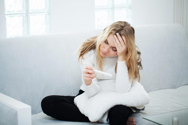 Test ciążowy. zmartwiona smutna kobieta patrzeje ciążowego test po rezultata