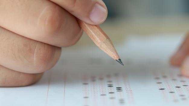 Test edukacji w koncepcji uniwersytetu lub szkoły średniej uczeń trzymając się za ręce ołówek do egzaminowania egzaminów na odpowiedź