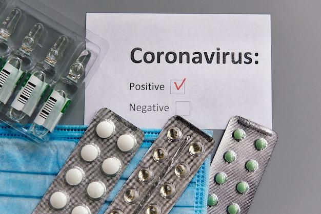 Test koronawirusa z wynikiem pozytywnym, pigułkami, ampułkami