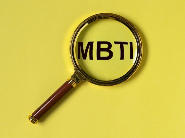 Test mbti akronimu typów osobowości przez soczewkę powiększającą na żółtym tle koncepcji psychologii