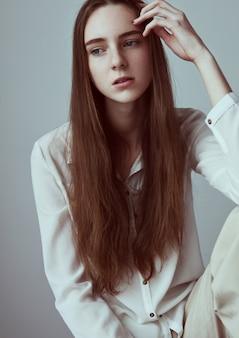 Test modelu z młodą piękną modelką z długimi włosami na sobie białą koszulę na szarym tle