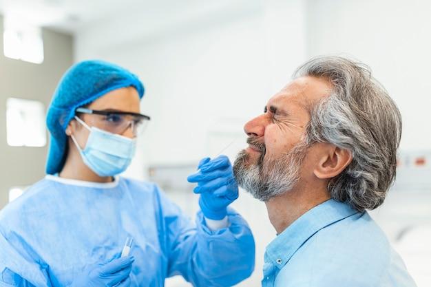 Test na koronawirusa pracownik medyczny pobierający wymaz z wirusa koronawirusa od potencjalnie zarażonego mężczyzny.