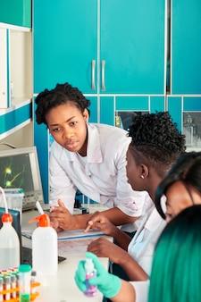 Test pcr kwasu nukleinowego do wykrywania nowego koronawirusa, nowe badanie krwi na przeciwciała. afrykańskie studentki medycyny, młodzi absolwenci badań, laboratorium badań medycznych przeprowadzają testy pacjentów, omawiają wyniki