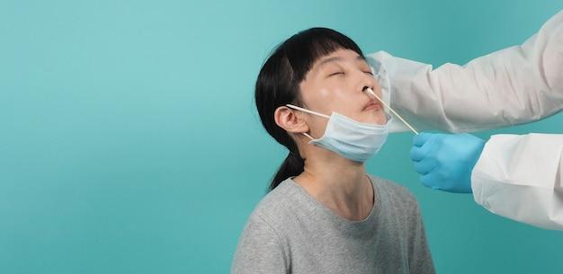 Test wymazowy covid 19. kobieta z testem pcr. test koronawirusa podczas epidemii. medyk pobierający próbkę do testów na obecność wirusów. studio strzał i niebieskie tło zielone. lekarz podczas badania wymazów z kombinezonu ppe.
