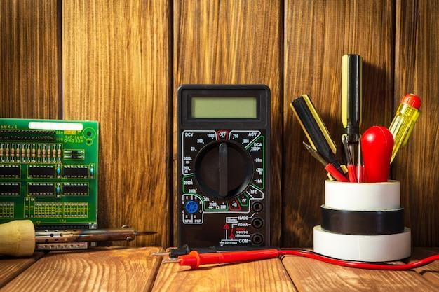 Tester elektryczny i zestaw narzędzi do naprawy elektroniki na drewniane tło.