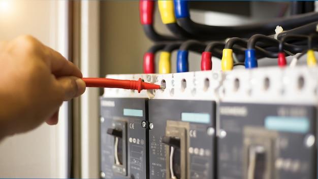 Tester pracy inżyniera elektryka mierzący napięcie i prąd linii elektroenergetycznej w sterowaniu szafką elektryczną.