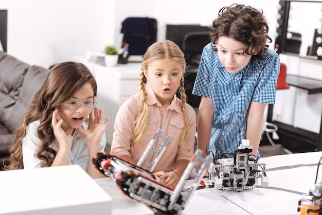 Testowanie nowoczesnej zabawki-robota. zainspirowani zszokowani i zdumieni uczniowie siedzący w szkole i testujący cyber-zabawkę podczas lekcji przedmiotów ścisłych