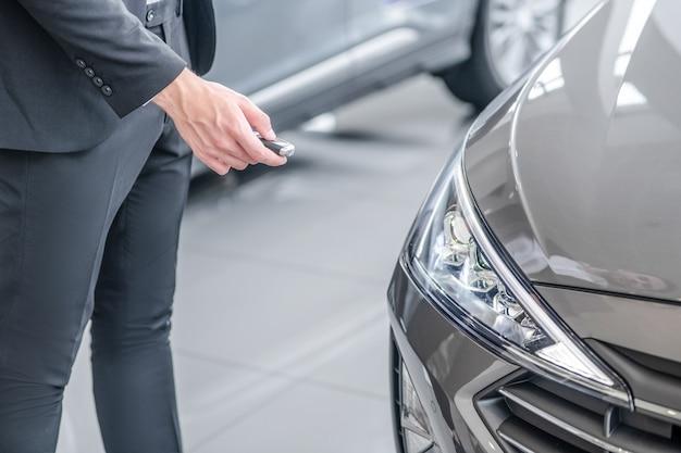 Testowanie. ręka mężczyzny w ciemnym garniturze stojąca w pobliżu nowego samochodu, naciskając brelok do samochodu, bez twarzy
