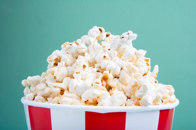 Testy świeżego popcornu w czerwony i biały kubek papierowy lub paski kubek papierowy oglądany z góry na białym tle na zielono