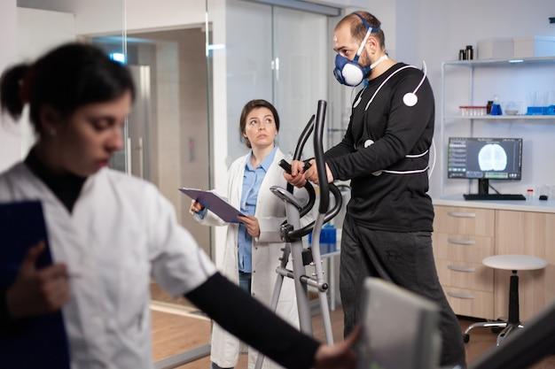 Testy wytrzymałościowe sportowców wyczynowych w laboratorium sportowym, bieganie z elektrodami na ciele w celu monitorowania. krzyż do pomiaru tętna cardio.
