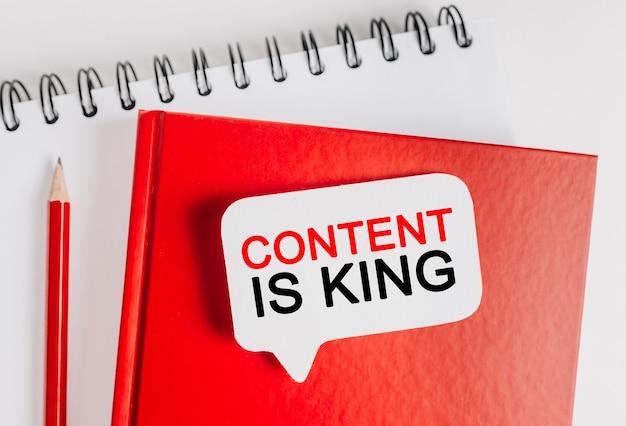 Text content is king na białej naklejce na czerwonym notatniku z tłem biurowym. mieszkanie leżało na koncepcji biznesu, finansów i rozwoju