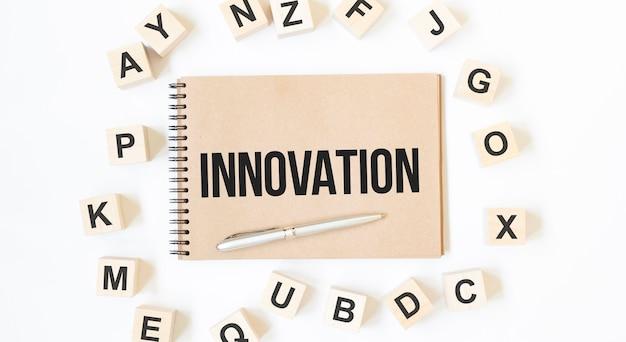 Text innovation na rzemieślniczym kolorowym notatniku z drewnianymi kostkami na białym tle