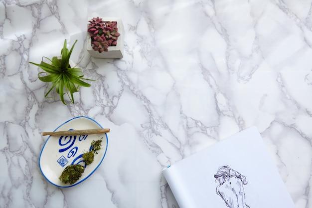 Thc cbd marihuana i kwiaty na popielniczce z nagą ilustracją na bloku rysunkowym
