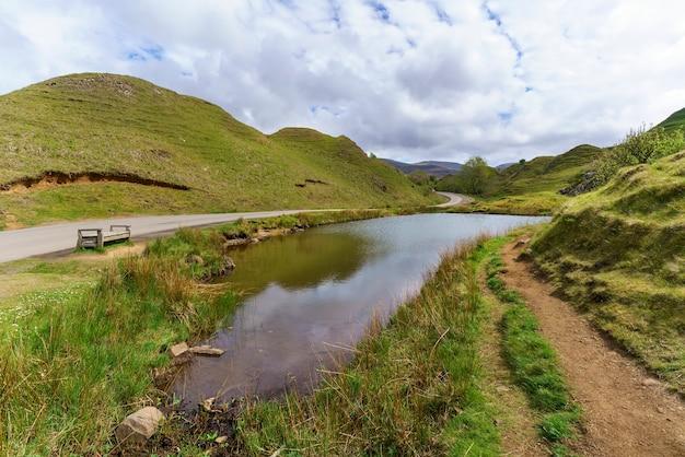 The fairy glen, kamienny krąg i krajobraz trawiastych, stożkowatych wzgórz latem, uig, szkocja
