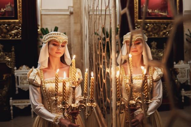 Thouhgtful księżniczka stoi z palącymi świecami przed lustrem