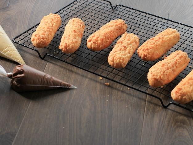 Tiger eclair/craquelin eclair, pyszny francuski deser z ciasta francuskiego nad czarnym drucianym stojakiem, świeżo upieczony, gotowy do napełnienia śmietaną. kopiuj miejsce na tekst/reklamę