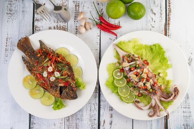 Tilapia smażona z sosem chili i kałamarnicą, cytryną i czosnkiem na talerzu na białym drewnianym stole.