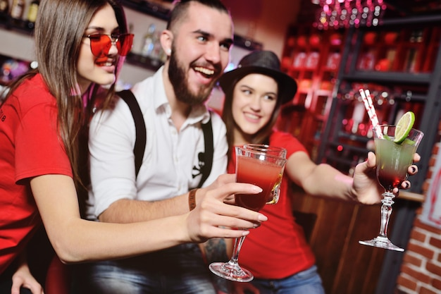 Time selfie. grupa przyjaciół na imprezie w klubie nocnym brzęczy szklankami z napojami alkoholowymi. szczęśliwi młodzi ludzie z koktajlami w pubie.