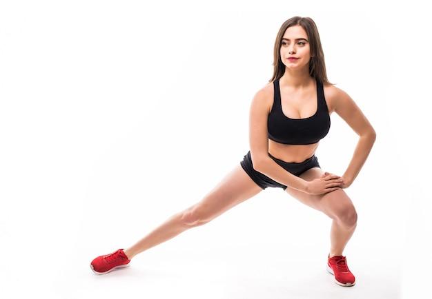 Tiny sportowa brunetka seksowna kobieta w czarnej odzieży sportowej ćwiczy dla silnego ciała sylwetki