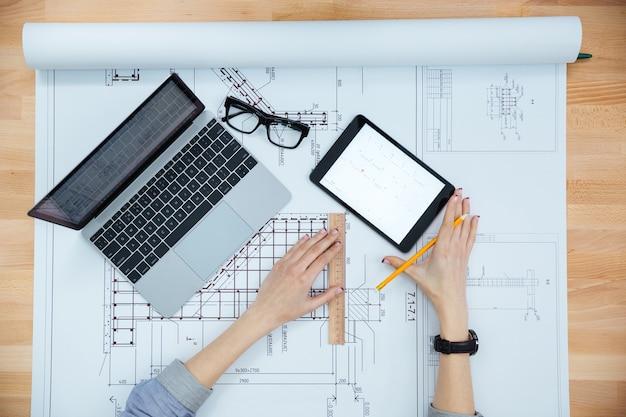 Tio widok młodej kobiety architekta pracującej i tworzącej plan
