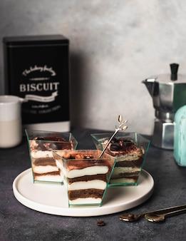 Tiramisu. tradycyjny włoski deser na szkle na szarej kamiennej ścianie ozdobiony czekoladowymi ziarnami kawy posypanymi proszkiem kakaowym