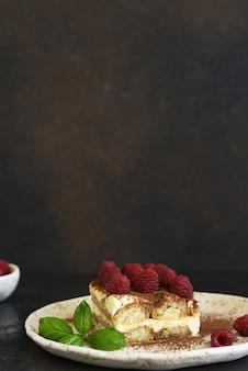 Tiramisu z malinami na ciemnym betonowym tle. klasyczny włoski deser to tiramisu.