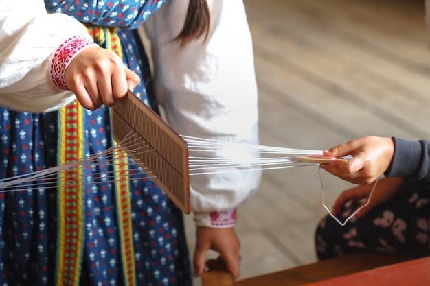 Tkactwo i produkcja ręcznie robionych tkanin z bliska. dłonie kobiet za krosnem tworzą płótno