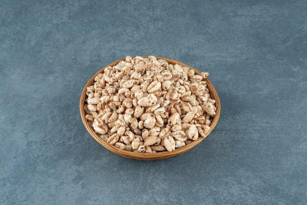Tkanie kosz z płatkami kukurydzianymi na marmurowym tle. zdjęcie wysokiej jakości