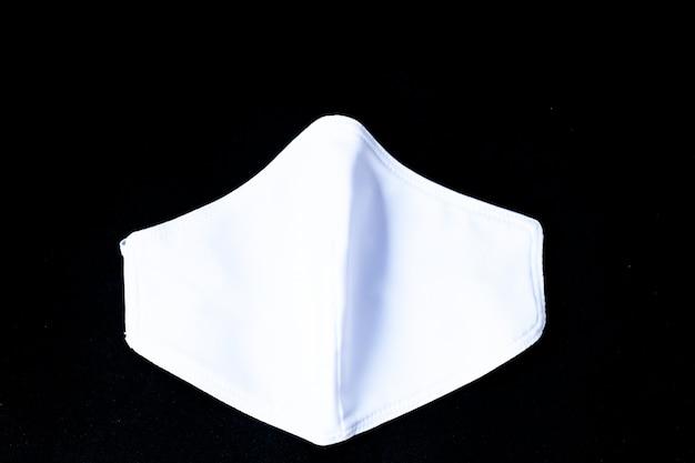Tkanina biała maska na białym tle na czarnym tle - w celu zapobiegania kurzu (pm 2.5), chorobom (koronawirus lub covid-19).