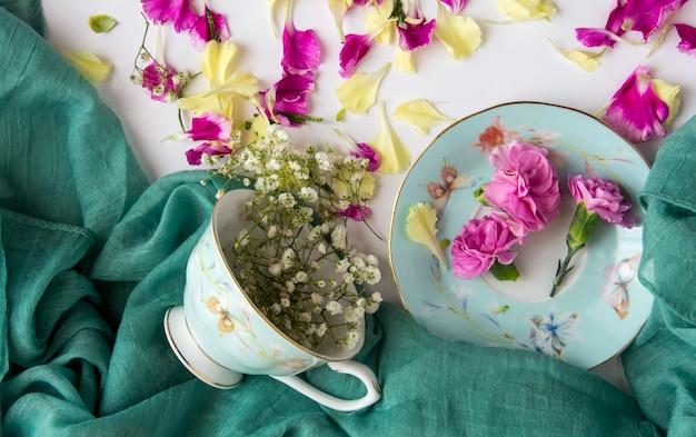 Tkanina, filiżanka i naturalne kwiaty i płatki