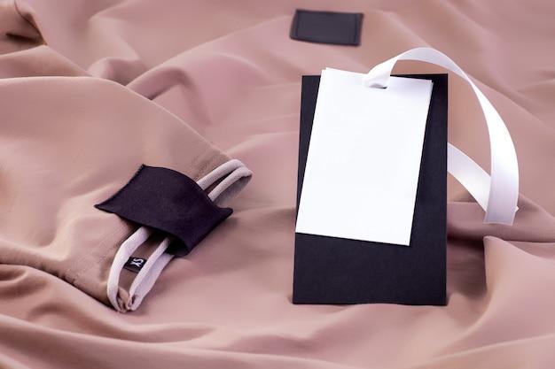 Tkanina makieta makro pusta czarna naszywka na logo marki na rękawie i papierowa etykieta na białej wstążce na beżowym ubraniu