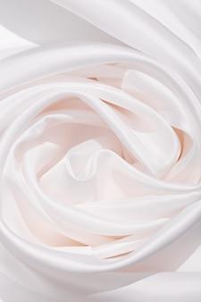 Tkanina tekstura tło białe kolory. jasny, satynowy materiał z marszczeniami