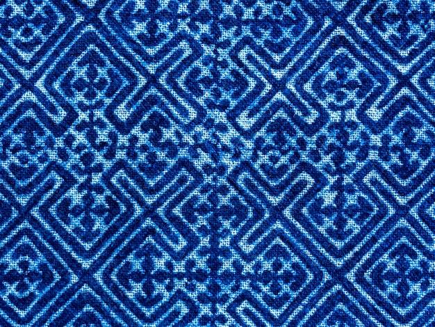 Tkanina w kolorze indygo w kolorze niebieskim. tekstura tkaniny barwionej w kolorze indygo z abstrakcyjnym etnicznym motywem graficznym.
