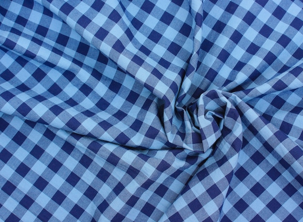 Tkanina w niebieską kratkę, skręcona spiralnie, widok z góry. bawełniany obrus o naturalnej fakturze. kratę, materiał koszuli.