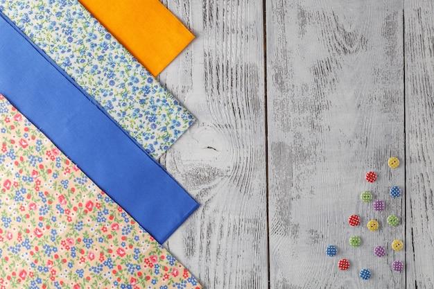Tkaniny bawełniane do szycia, koronki i akcesoria do robótek ręcznych na drewnianym tle.